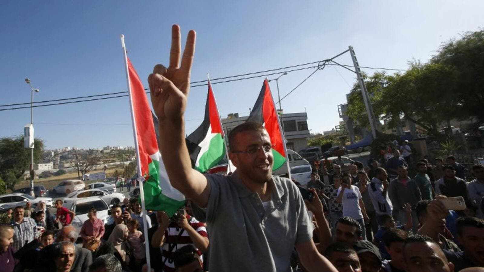 Mohammed al-Qiq flashes a peace sign as he arrives back to his village in the West Bank. (AFP/Hazem Bader)