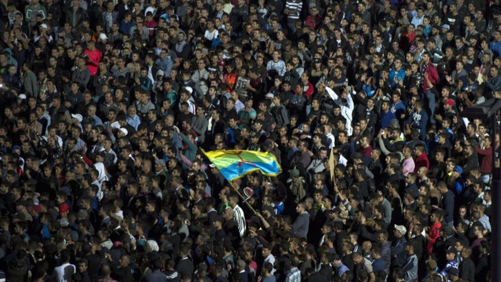 Protesters wave the Amazigh (Berber) flag as they shout slogans in the northern city of Al Hoceima on October 30, 2016, following the death of fishmonger Mouhcine Fikri, who was crushed to death on October 28 in a rubbish truck in Al Hoceima. (AFP/Fadel Senna)