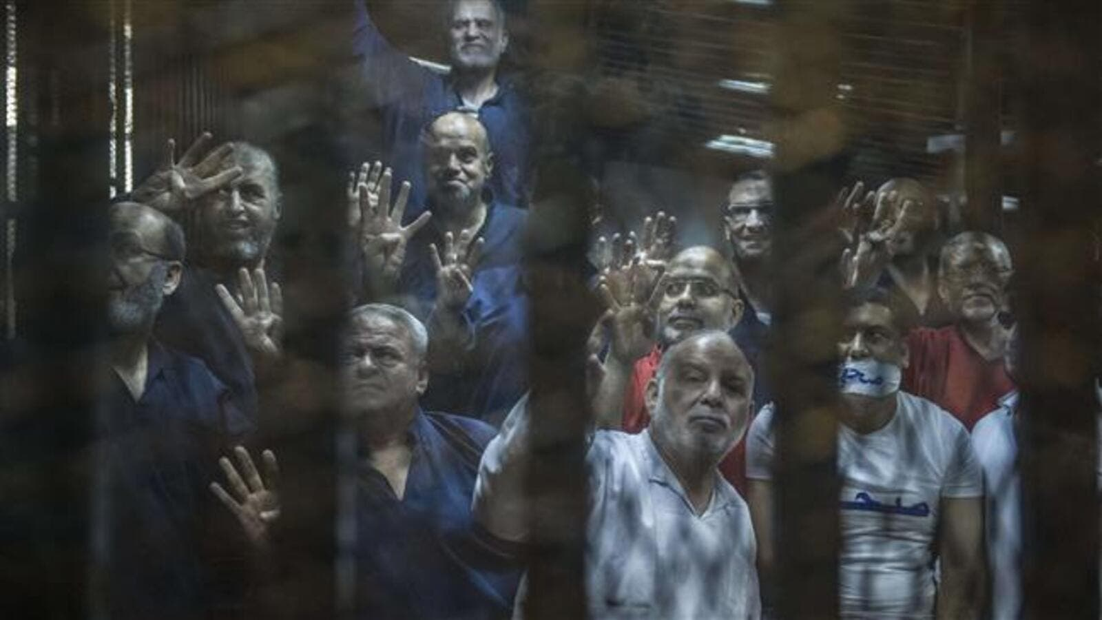 Senior figures of Egypt's Muslim Brotherhood gesture from the defendants cage during their trial at the police academy on the outskirts of Cairo on June 2, 2015. (AFP/File)
