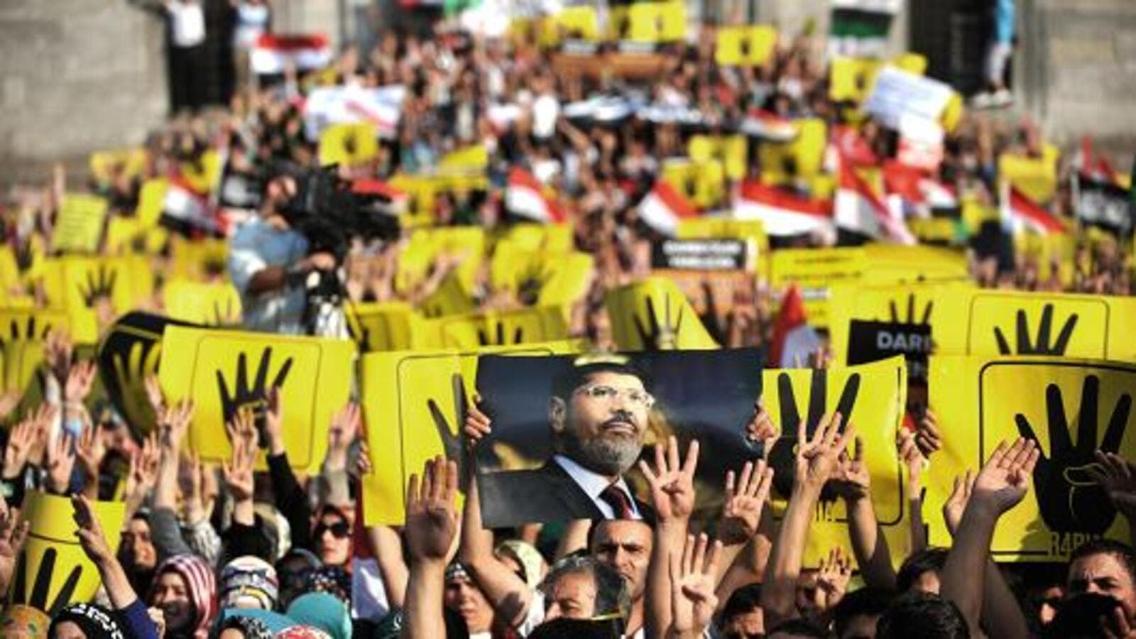Supporters of the Egyptian Muslim Brotherhood gesture support for Morsi. (AFP/File)