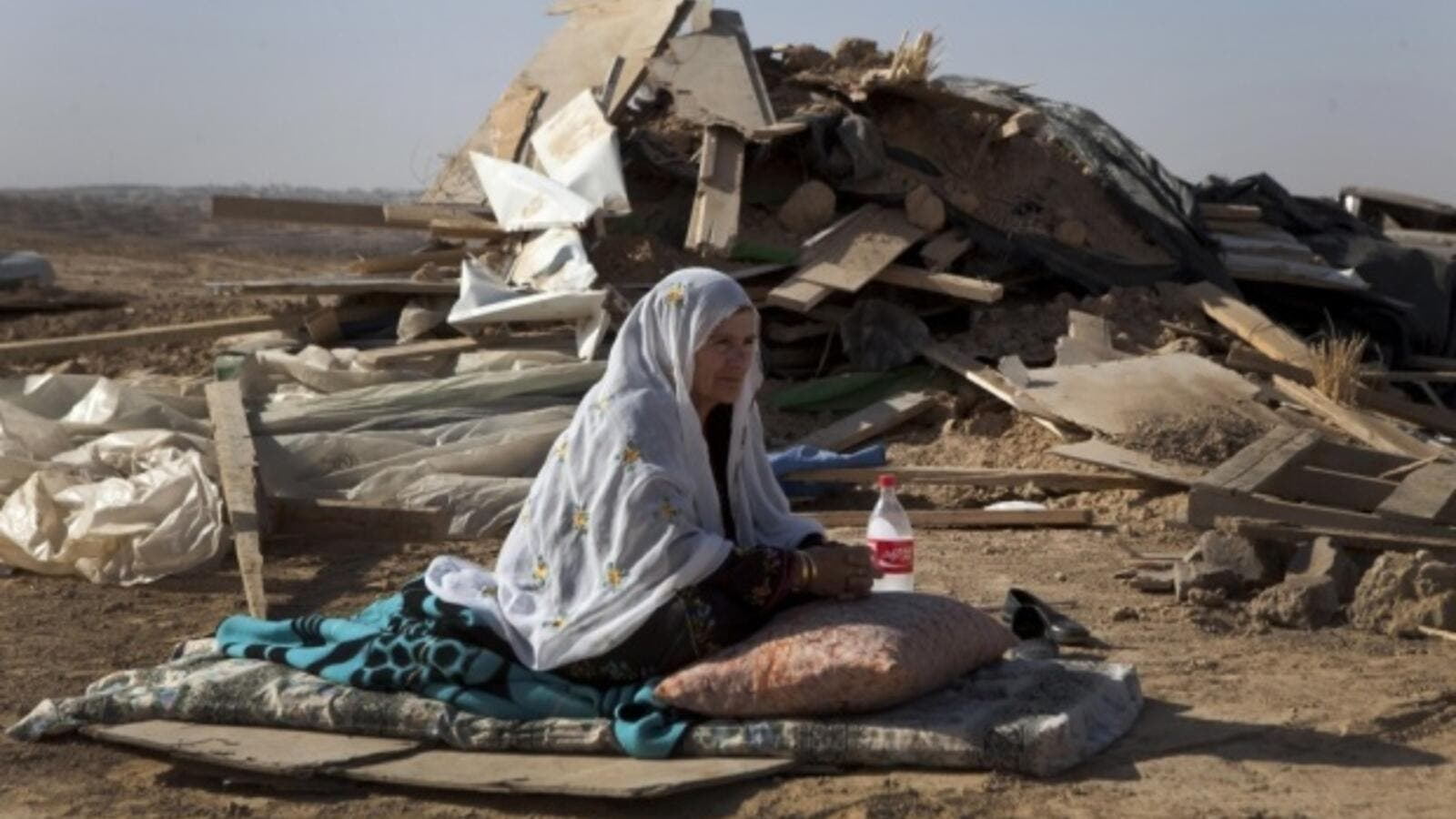 A Bedouin woman sits in front of a razed home. (AFP/File)