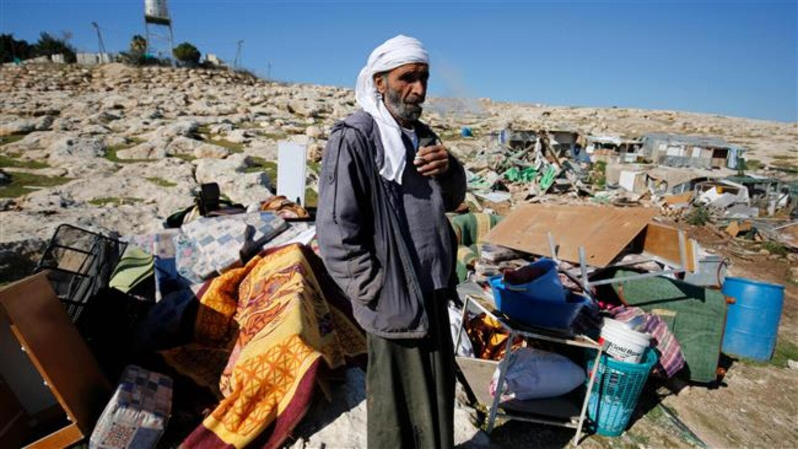 Palestinian Bedouin Abu Nawar stands next to the remains of makeshift homes that were demolished by Israeli forces east of al-Quds (Jerusalem) in the occupied West Bank, on January 6, 2016. (AFP/File)