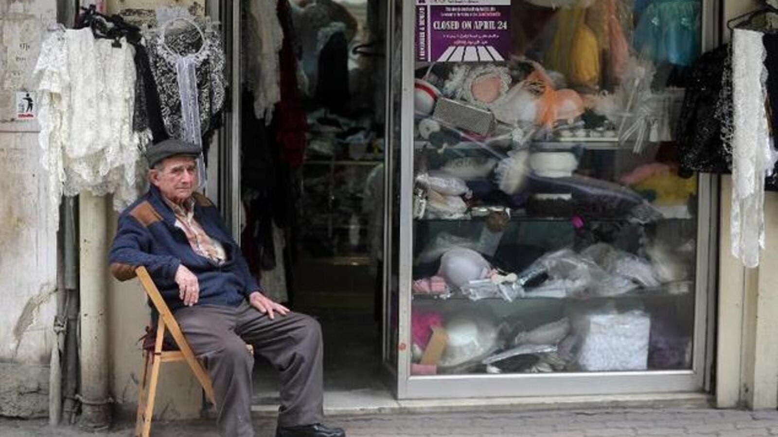A Lebanese-Armenian man sits next to his shop in the Burj Hammoud area of Beirut. (AFP/File)