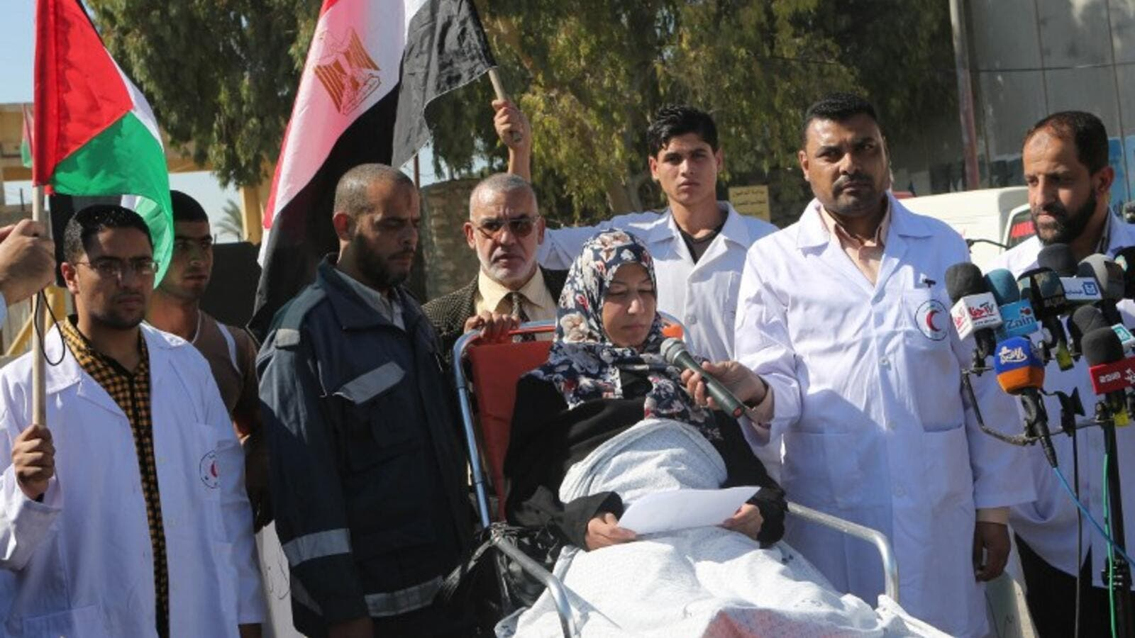 Palestinian medical staff stand next to a patient as she speaks to the media, calling on Egypt to open the Rafah crossing in the southern Gaza Strip on November 6, 2014. (AFP/Said Khatib)