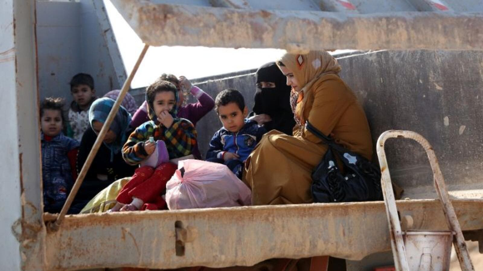 Iraqi women and children sit in the back of a truck at an army checkpoint at Ayn al-Tamer crossing at the entrance to Karbala province on January 6, 2014. (AFP/Ahmad al-Rubaye)