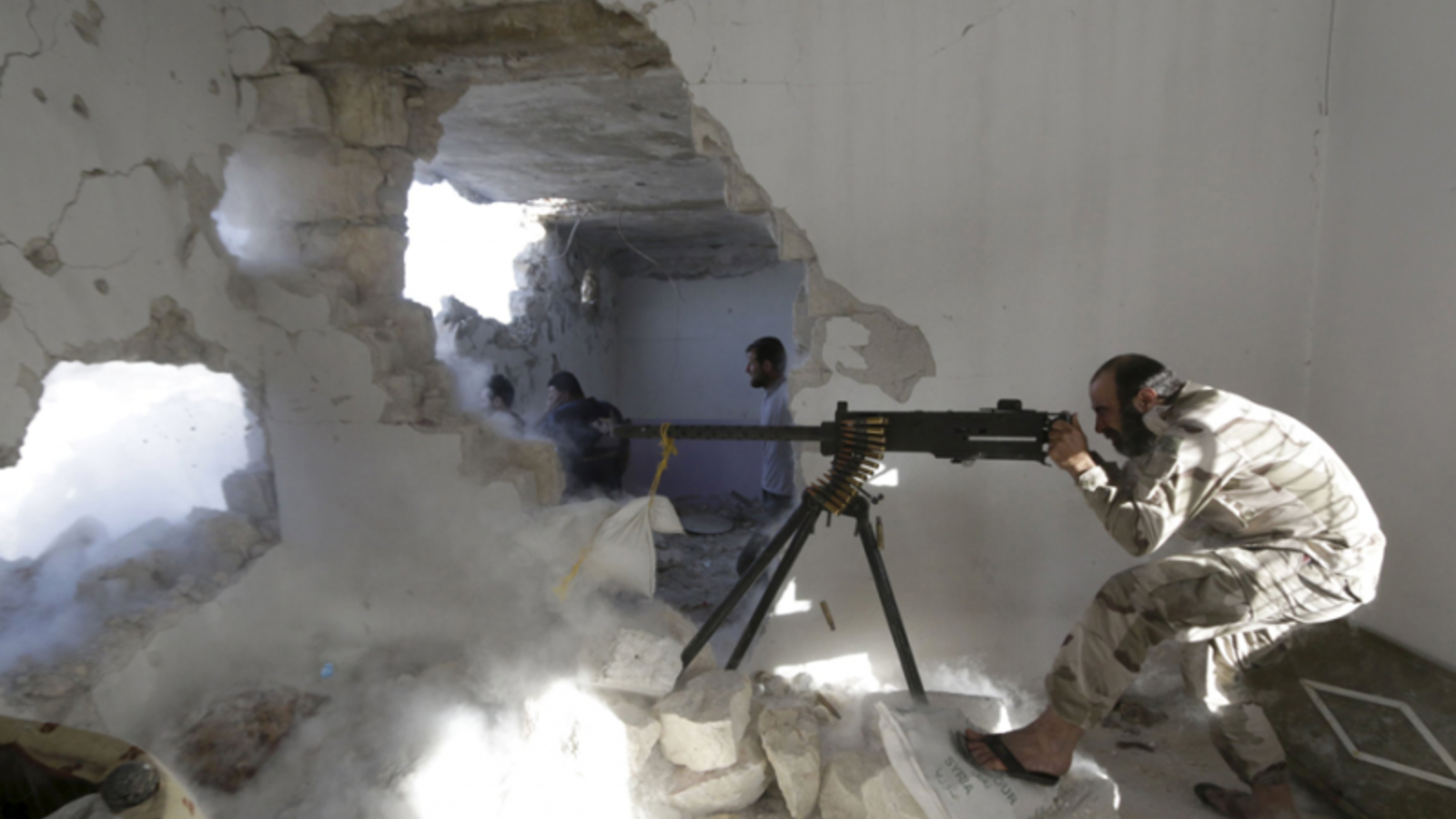 A Free Syrian Army fighter fires a weapon inside a damaged building during clashes with forces from the Syrian regime. (AFP/File)