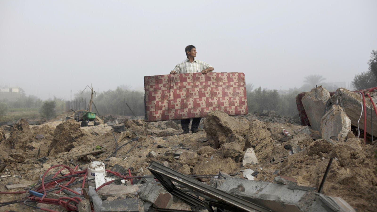 A Palestinian man carries a mattress at the rubble of a destroyed building following a military attack on his home. (AFP/File)