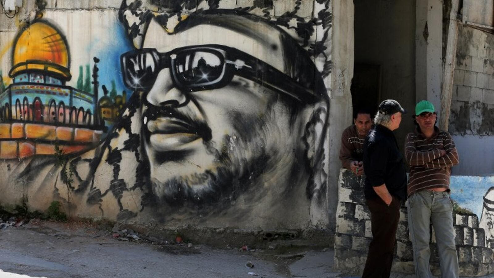 Palestinian refugees stand next to graffiti bearing a portrait of late Palestinian President Yasser Arafat at the Ain Al-Helweh refugee camp. (AFP/File)