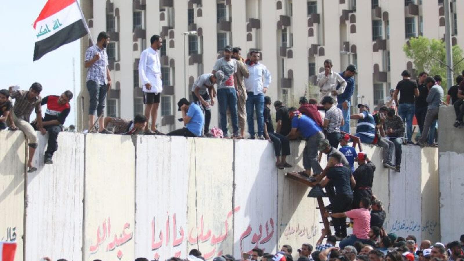 Iraqi protesters climb over a concrete wall surrounding the parliament after breaking into Baghdad. (AFP/File)