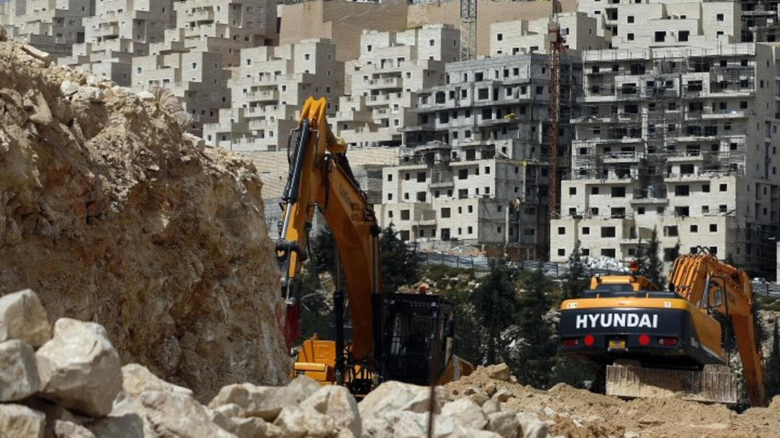 Israeli construction cranes and excavators at a building site in the Israeli settlement of Neve Yaakov, in the northern area of east Jerusalem on March 29, 2016. (AFP/Ahmad Gharabli)