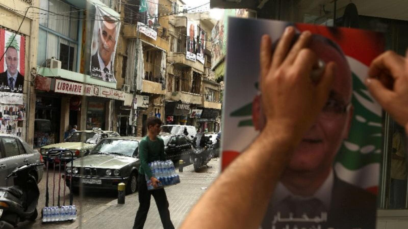 A Lebanese man puts up a poster of a candidate in the Beirut municipal elections. (AFP/File)