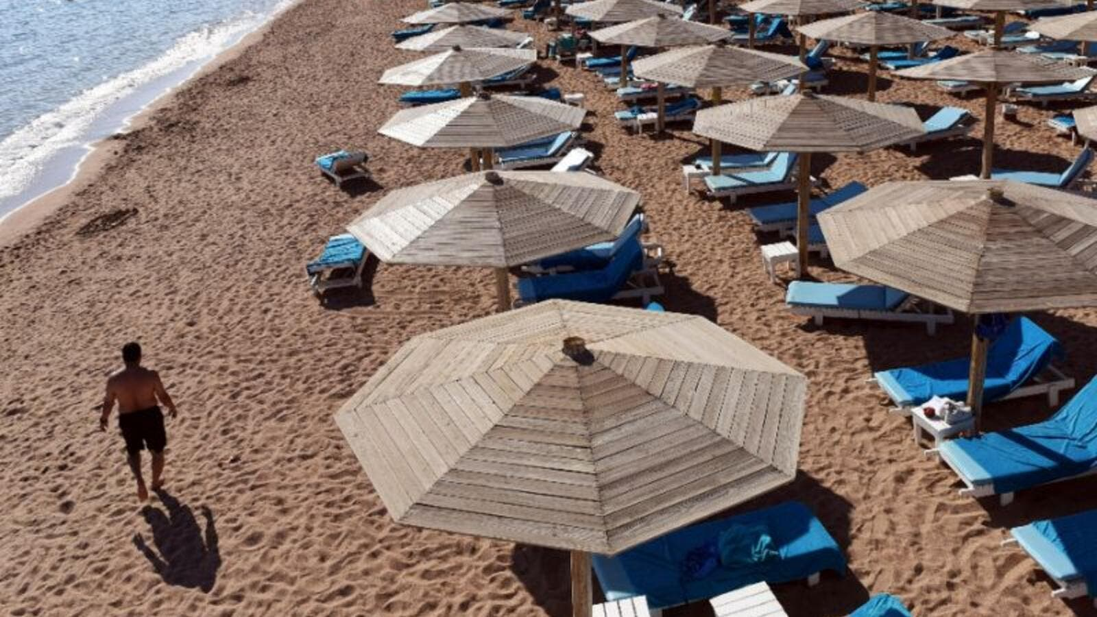 A tourist walks past empty sunbeds on a beach in Egypt. (AFP/File)