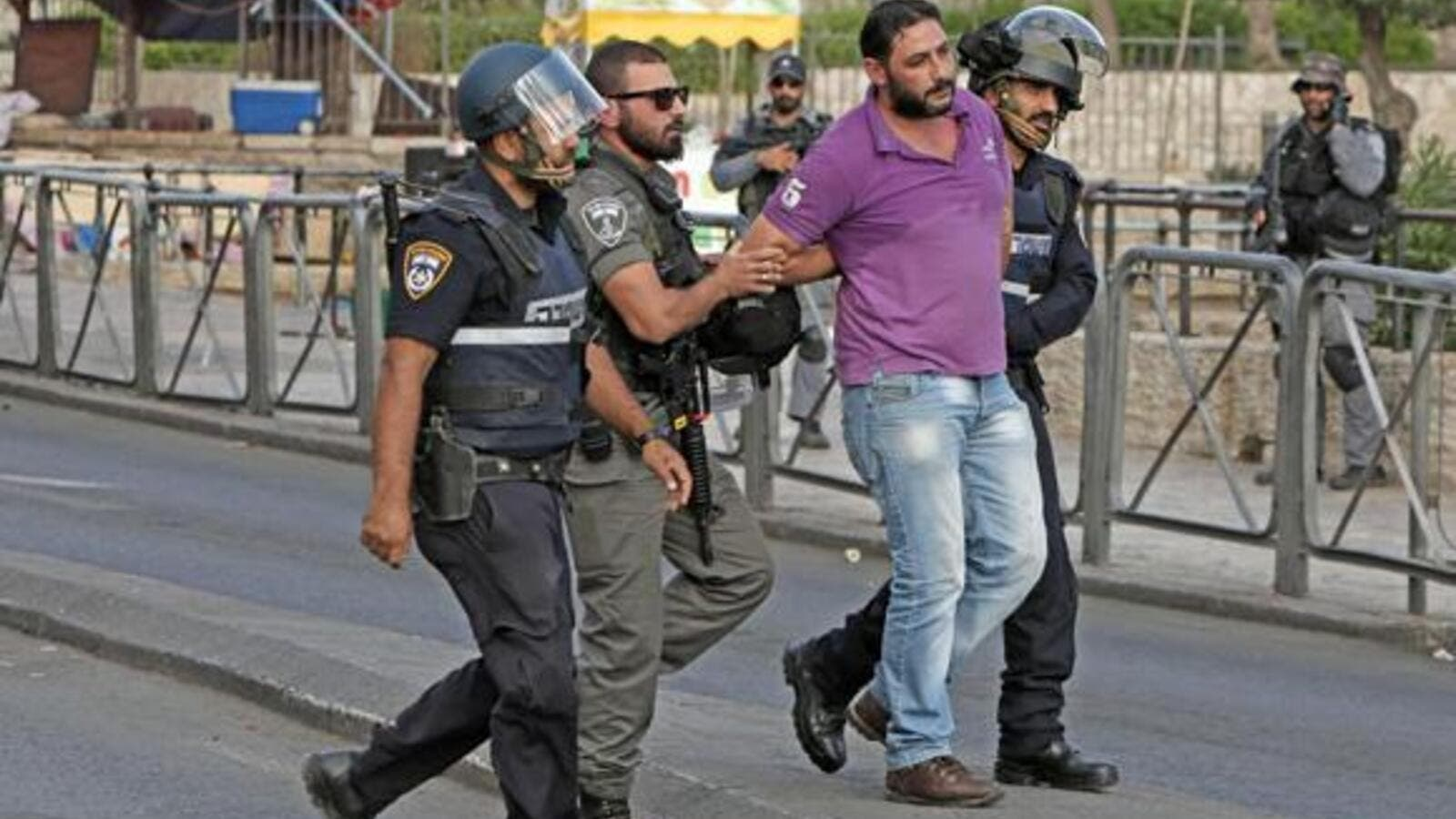Israeli policemen detain a Palestinian, at the site where two Israeli police officers were stabbed. (AFP/File)