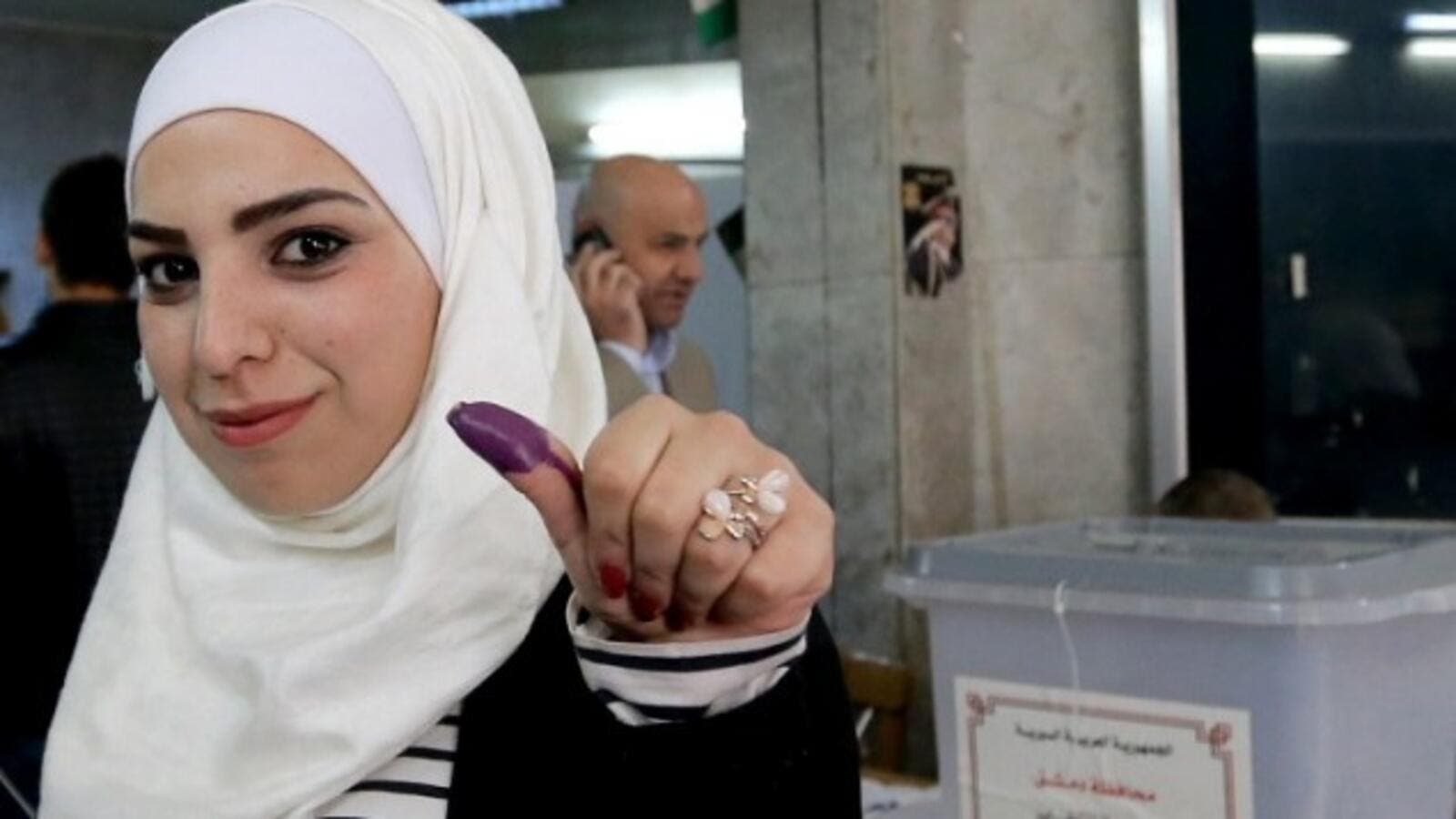 A Syrian woman shows her ink-stained thumb after voting in parliamentary elections. (AFP/File)
