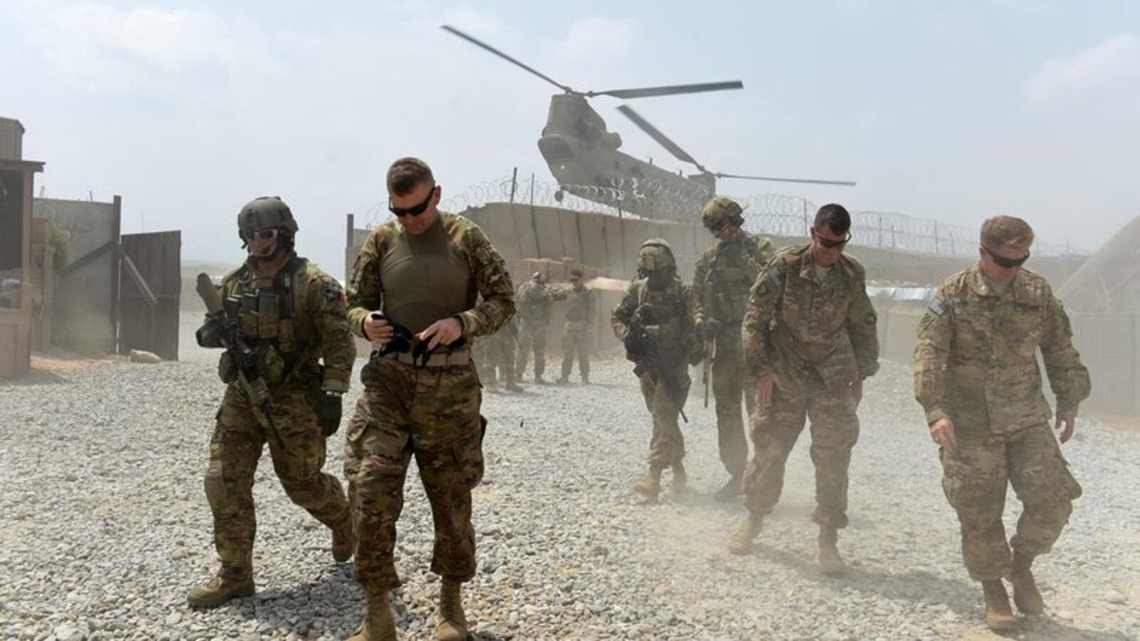 U.S. Army soldiers walk as a NATO helicopter flies overhead at coalition force Forward Operating Base (FOB) Connelly in the Khogyani district in the eastern province of Nangarhar on August 13, 2015. (AFP/Wakil Kohsar)