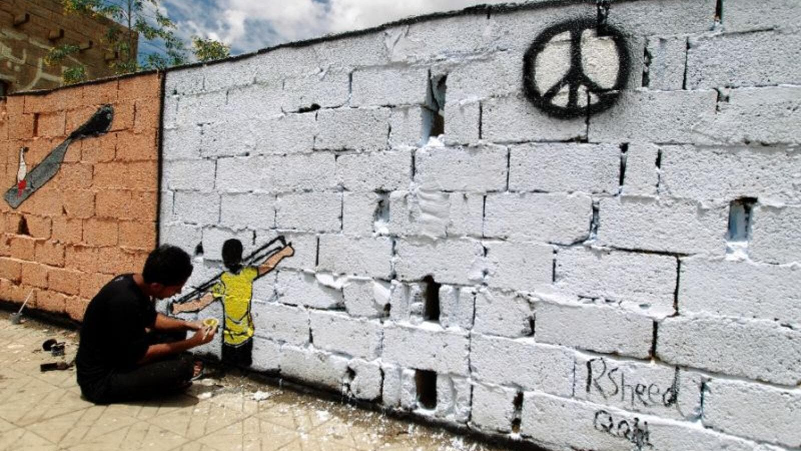 A Yemeni artist sprays graffiti on a wall in the capital Sanaa in support of peace. (AFP/File)