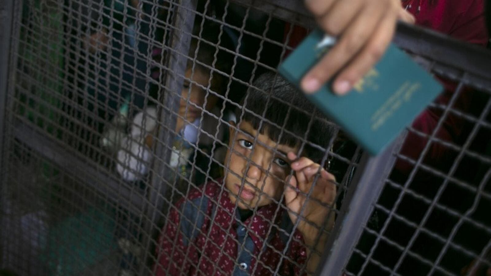 A Palestinian child looks through a barrier as he waits at the Rafah border crossing with Egypt, in the southern Gaza Strip, after it was opened for two days by Egyptian authorities, on May 11, 2016. (AFP/Said Khatib)