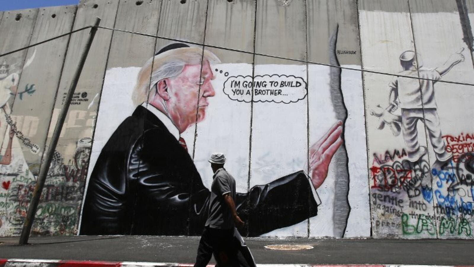 'I'm going to build you a brother' reads new West Bank separation wall graffito (AFP)
