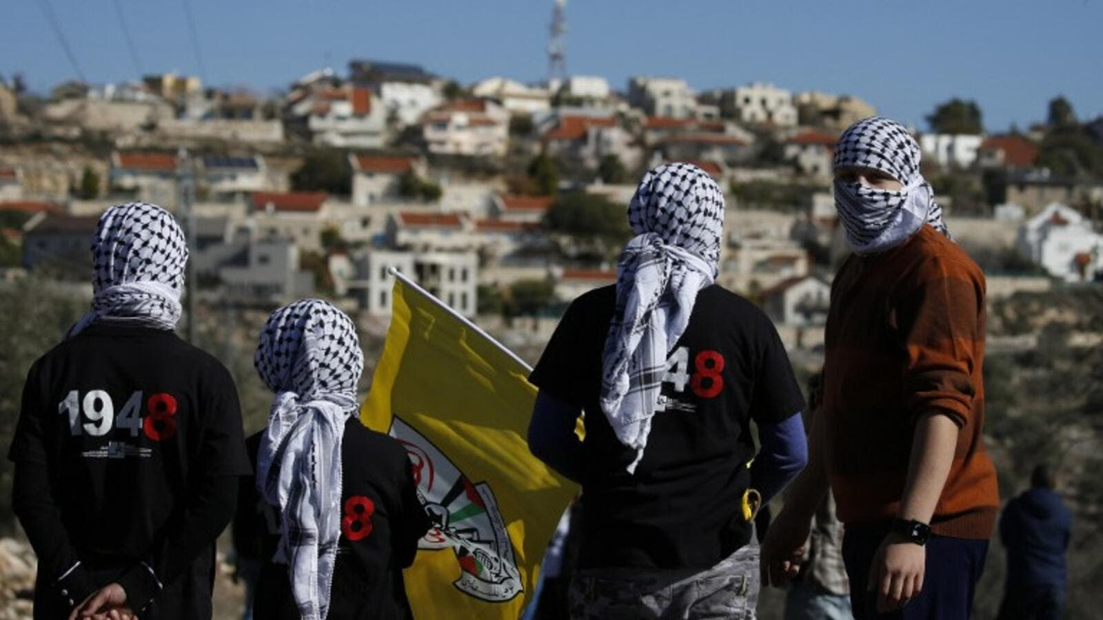 This file photo taken on December 30, 2016 shows Palestinian protestors stand facing the Israeli settlement of Qadumim (Kedumim) during clashes with Israeli security forces following a demonstration against the expropriation of Palestinian land by Israel in the village of Kfar Qaddum, near Nablus, in the occupied West Bank. (AFP/Jaafar Ashtiyeh)