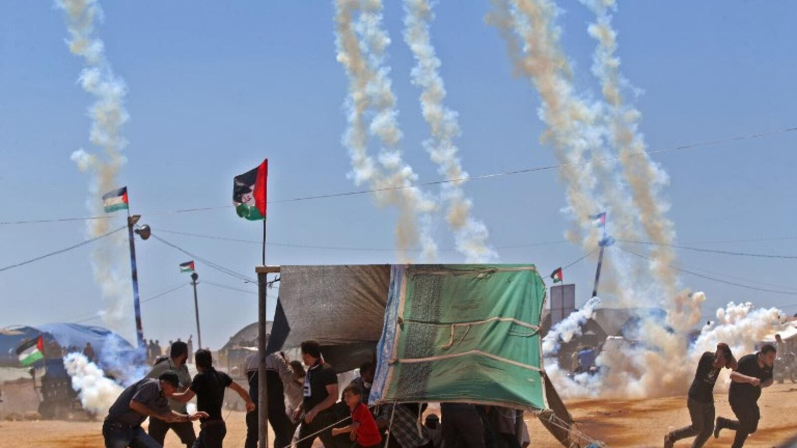Palestinians run for cover from tear gas near the border between Israel and the Gaza Strip, east of Jabalia. (Mohammed ABED/ AFP)