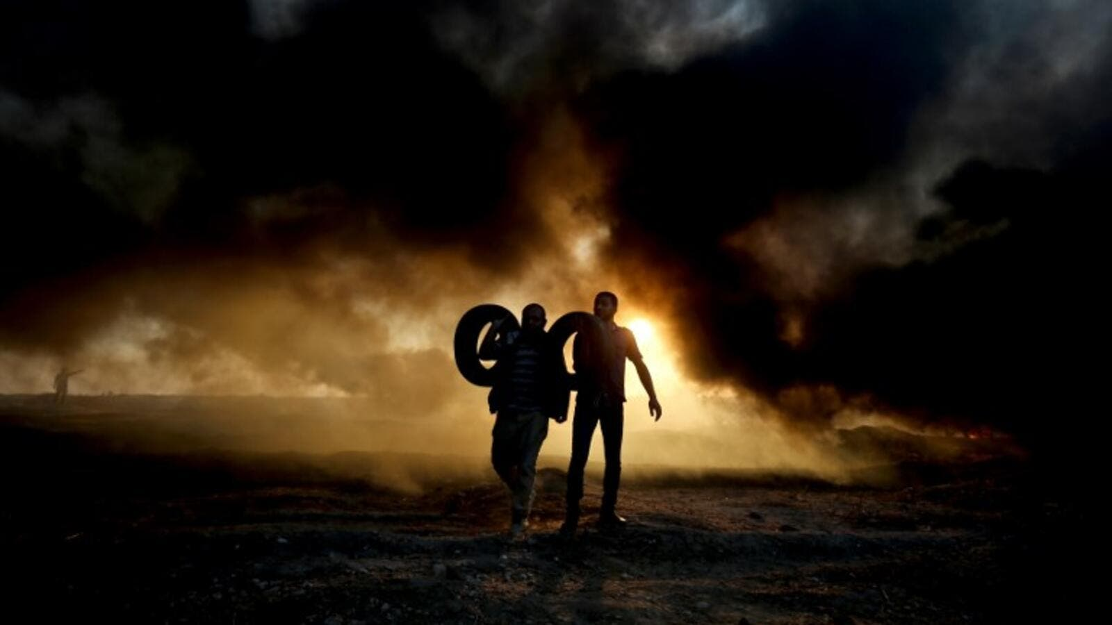 Palestinian protesters carry tyres as smoke billows from burning tyres at the Israel-Gaza border, east of Gaza city. (SAID KHATIB / AFP)
