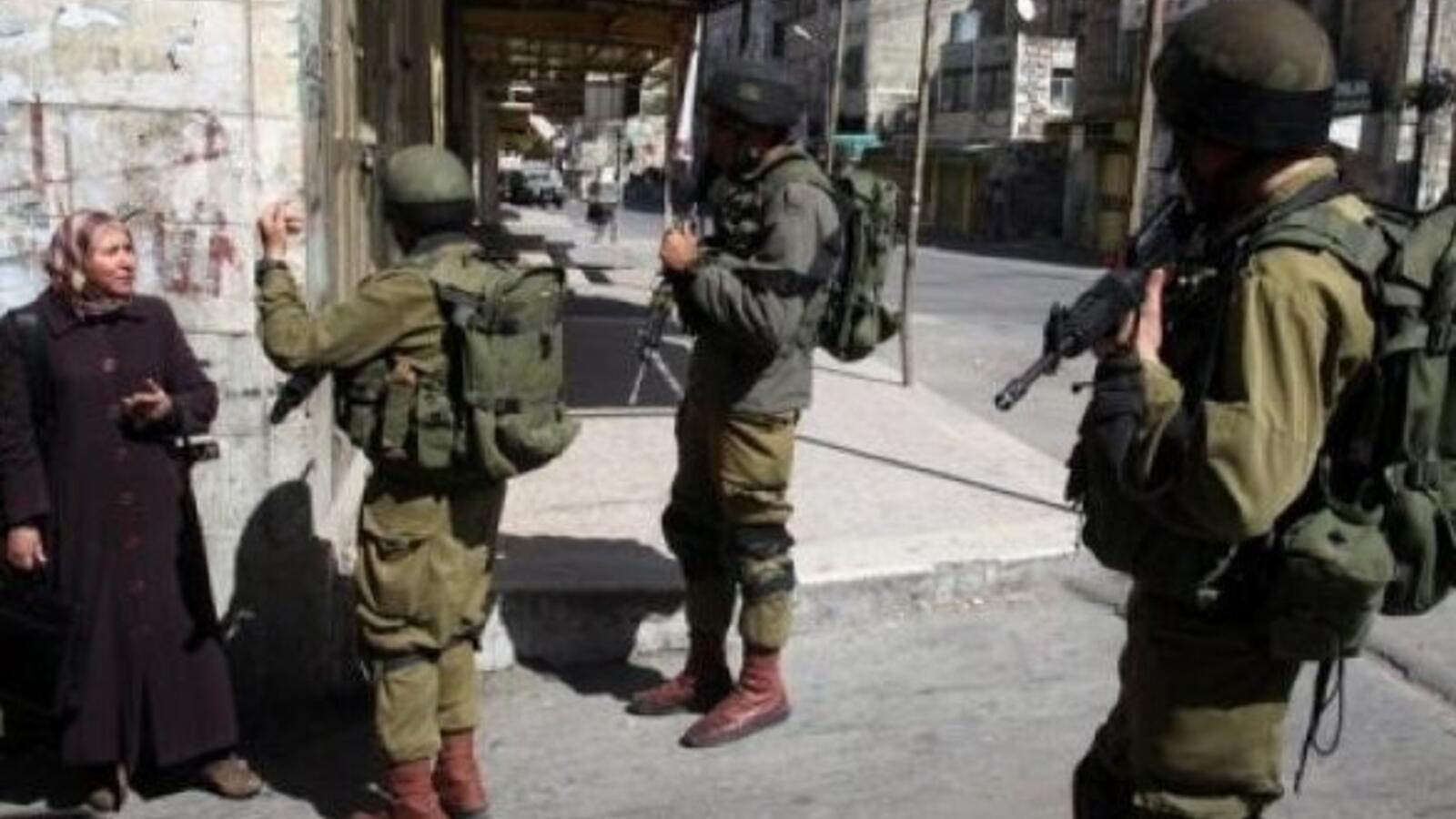 Israeli soldiers stop a Palestinian woman in the Palestinian side of the city of Hebron. (AFP/ File)