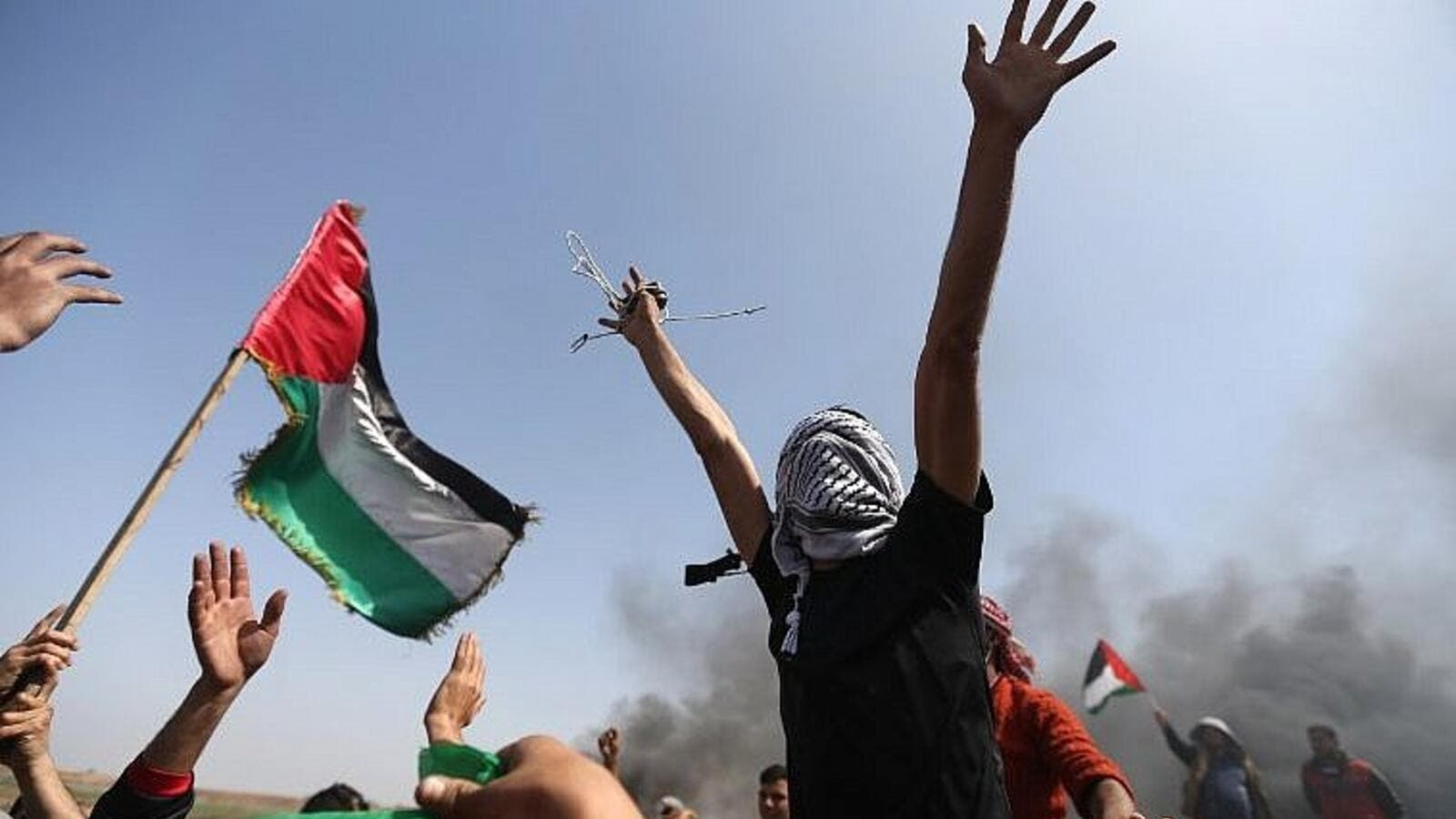 Palestinian demonstrators wave their national flag and shout slogans against Israeli security forces during a protest on the Israel-Gaza border in the northern Gaza Strip on April 6, 2018. (AFP/Mohammed Abed)