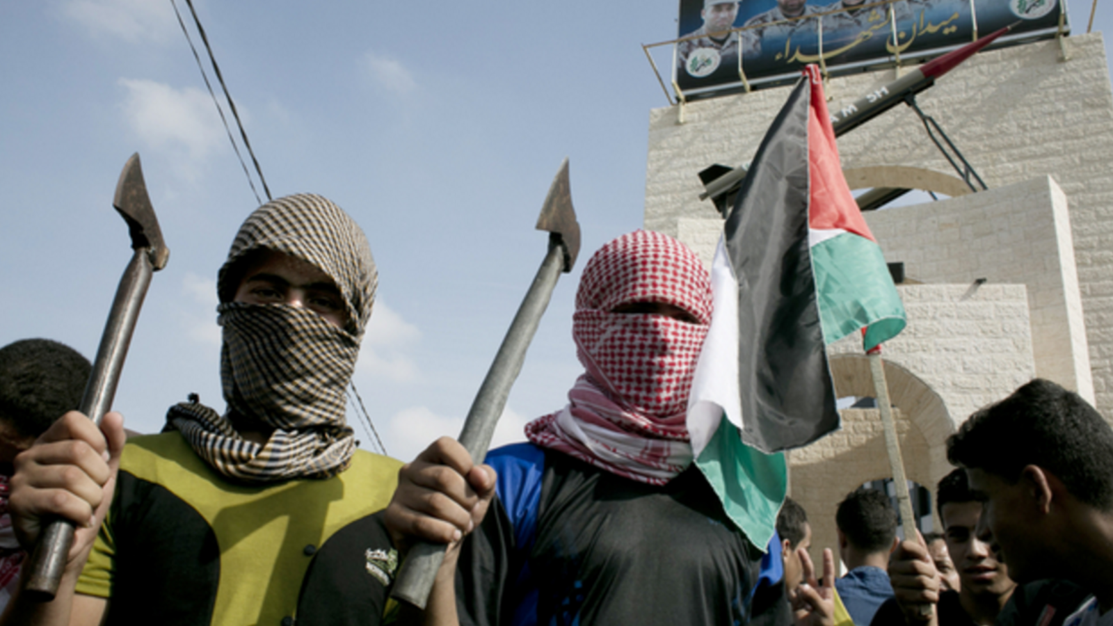 Palestinian students in checkered keffiyehs holding axes. (photo: AFP)