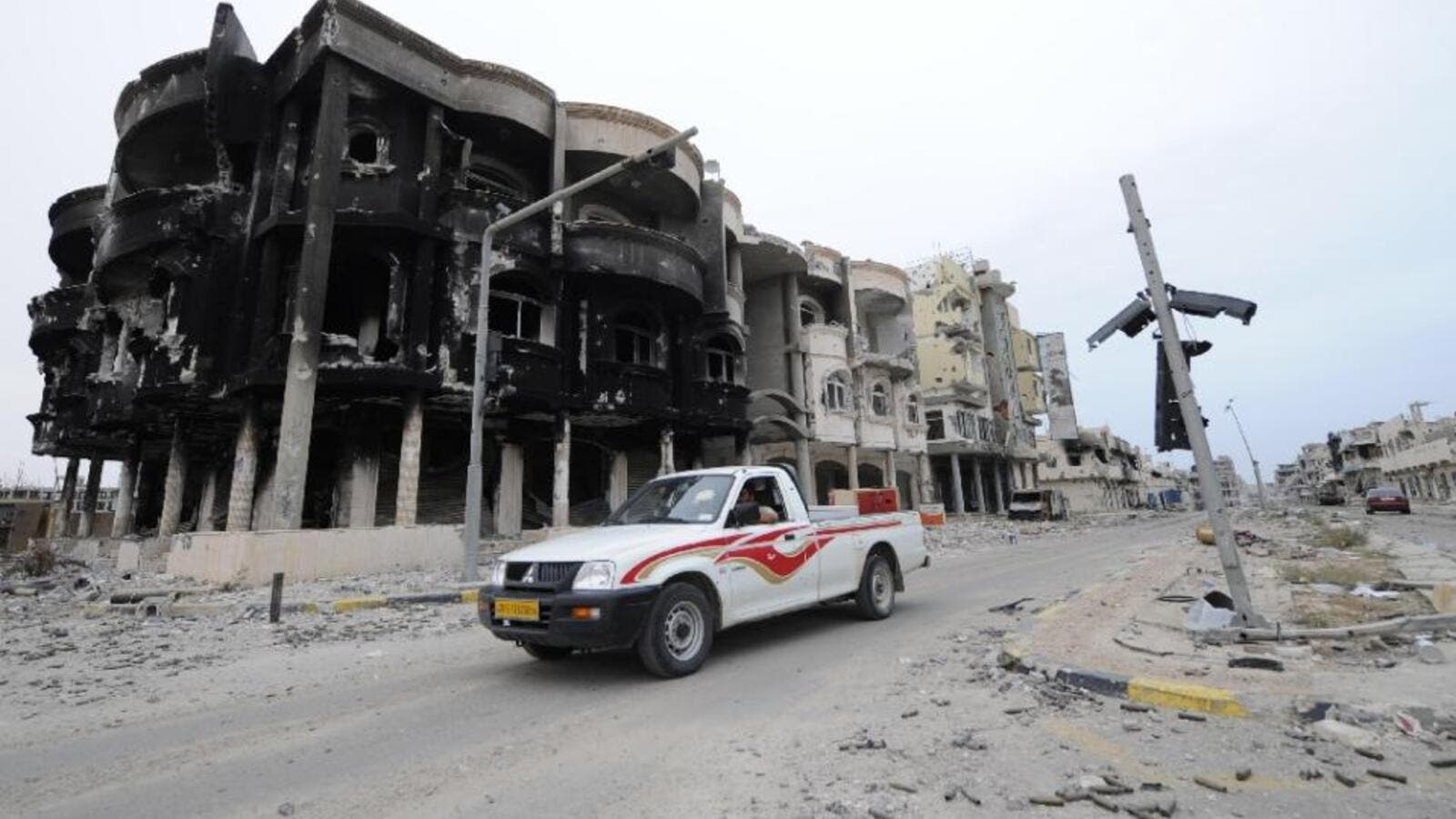 A resident driver past a burned building in Sirte, Libya. (AFP/File)