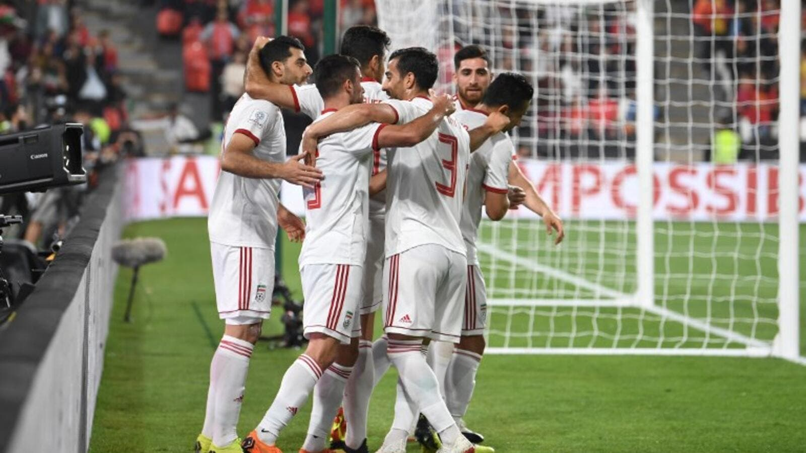 Iran's players celebrate their opening goal during the 2019 AFC Asian Cup quarter-final football match between China and Iran at the Mohammed Bin Zayed Stadium Stadium in Abu Dhabi on January 24, 2019.