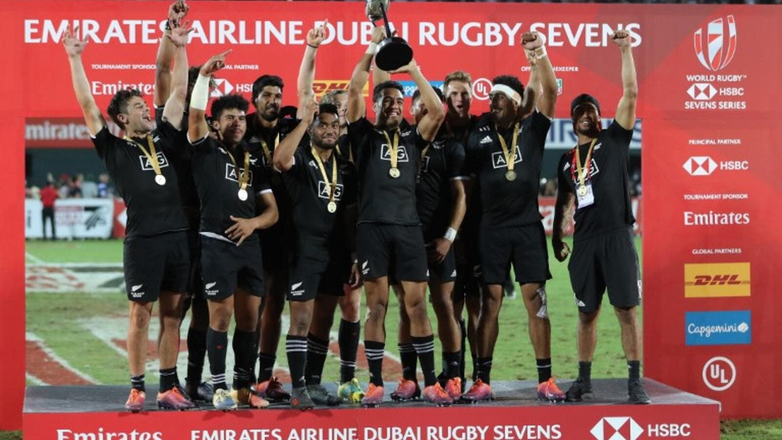 New Zealand's players celebrate with the trophy of the Men's Sevens World Rugby Dubai Series Cup after the Final match between USA an New Zealand on December 01, 2018.