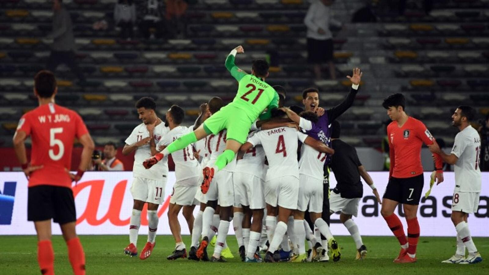 Qatar's players celebrate their victory during the 2019 AFC Asian Cup quarter-final football match between South Korea and Qatar at Zayed Sports City in Abu Dhabi on January 25, 2019.