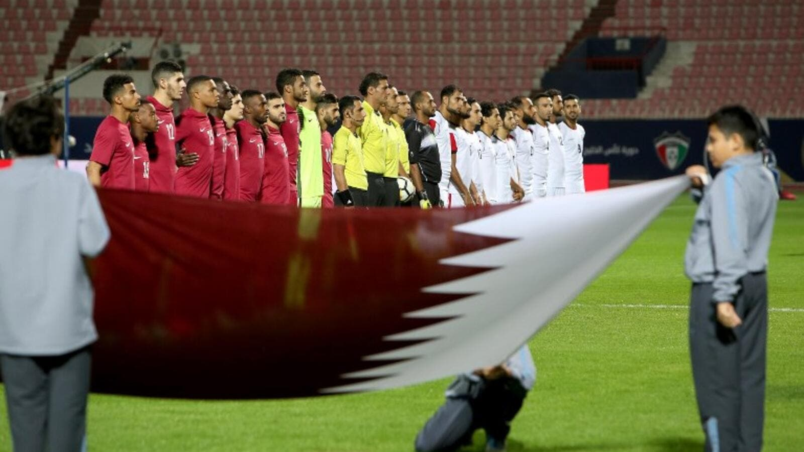 Qatar's and Yemen's starting eleven pose for a group picture ahead of the 2017 Gulf Cup of Nations football match between Qatar and Yemen at the Sheikh Jaber al-Ahmad Stadium in Kuwait City on December 23, 2017.