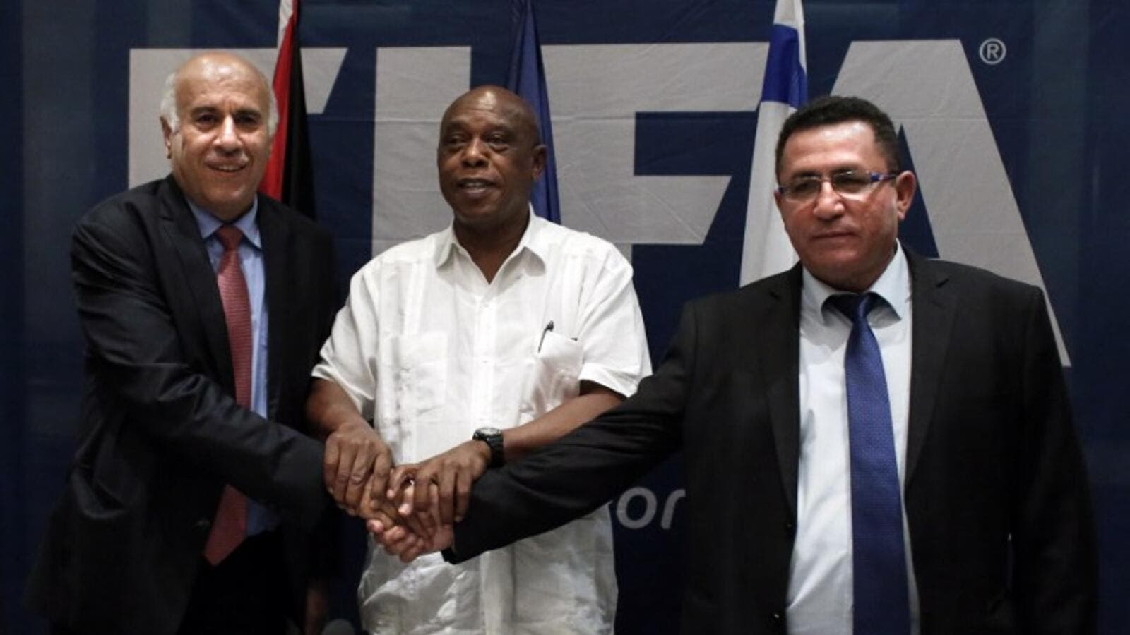 (From L-R) Palestinian Football Association president Jibril Rajoub, Chairman of the FIFA Monitoring Committee Israel-Palestine Tokyo Sexwale and Israel's Football Association president Ofer Eini, shake hands at the end of a press conference in the West Bank city of Jericho. AFP PHOTO / THOMAS COEX