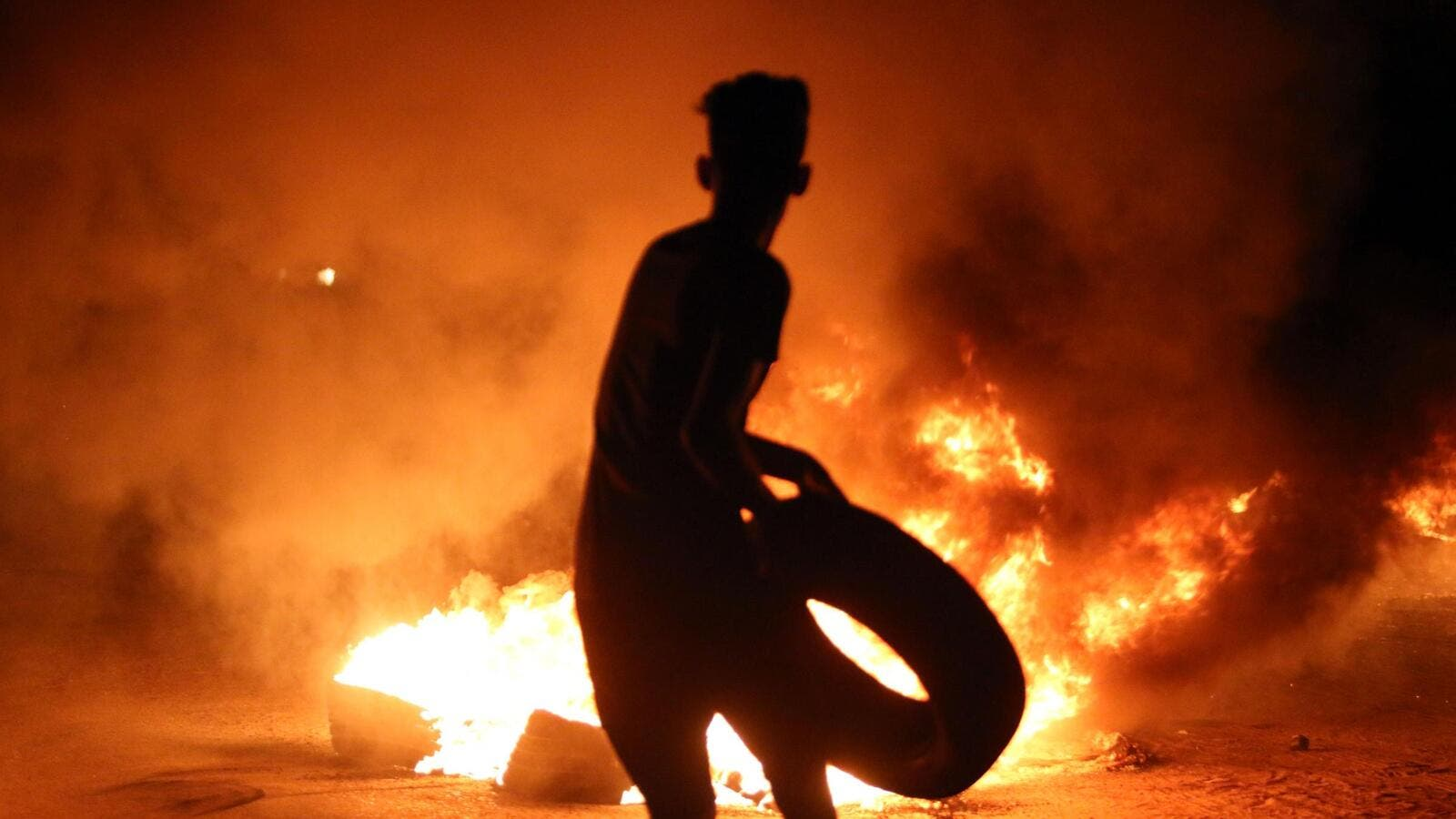 A resident of Basra holds up a tire outside the burning Iranian Consulate (AFP/FILE)
