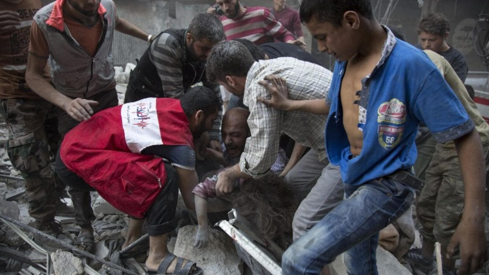 Syrians surround a man as he cries over the body of his child after she was pulled out from the rubble of a budling following government forces air strikes in the rebel held neighbourhood of Al-Shaar in Aleppo on September 27, 2016. (AFP/Karam al-Masri)