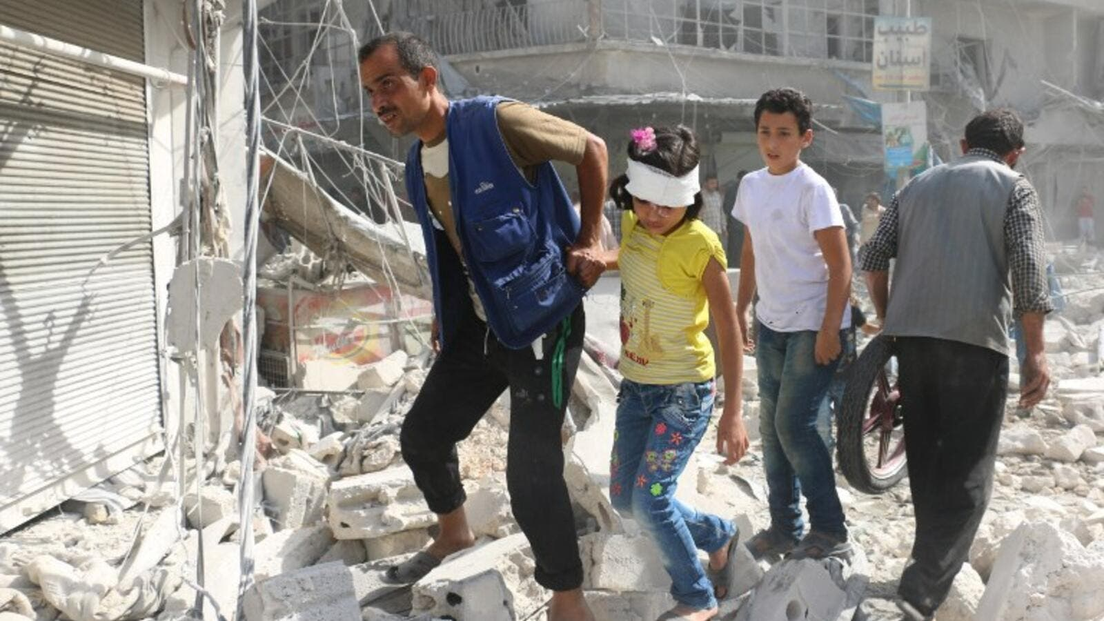 Syrians walk over rubble following air strikes on the rebel-held Fardous neighbourhood of the northern embattled Syrian city of Aleppo on October 12, 2016. (AFP/Ameer Alhalbi)