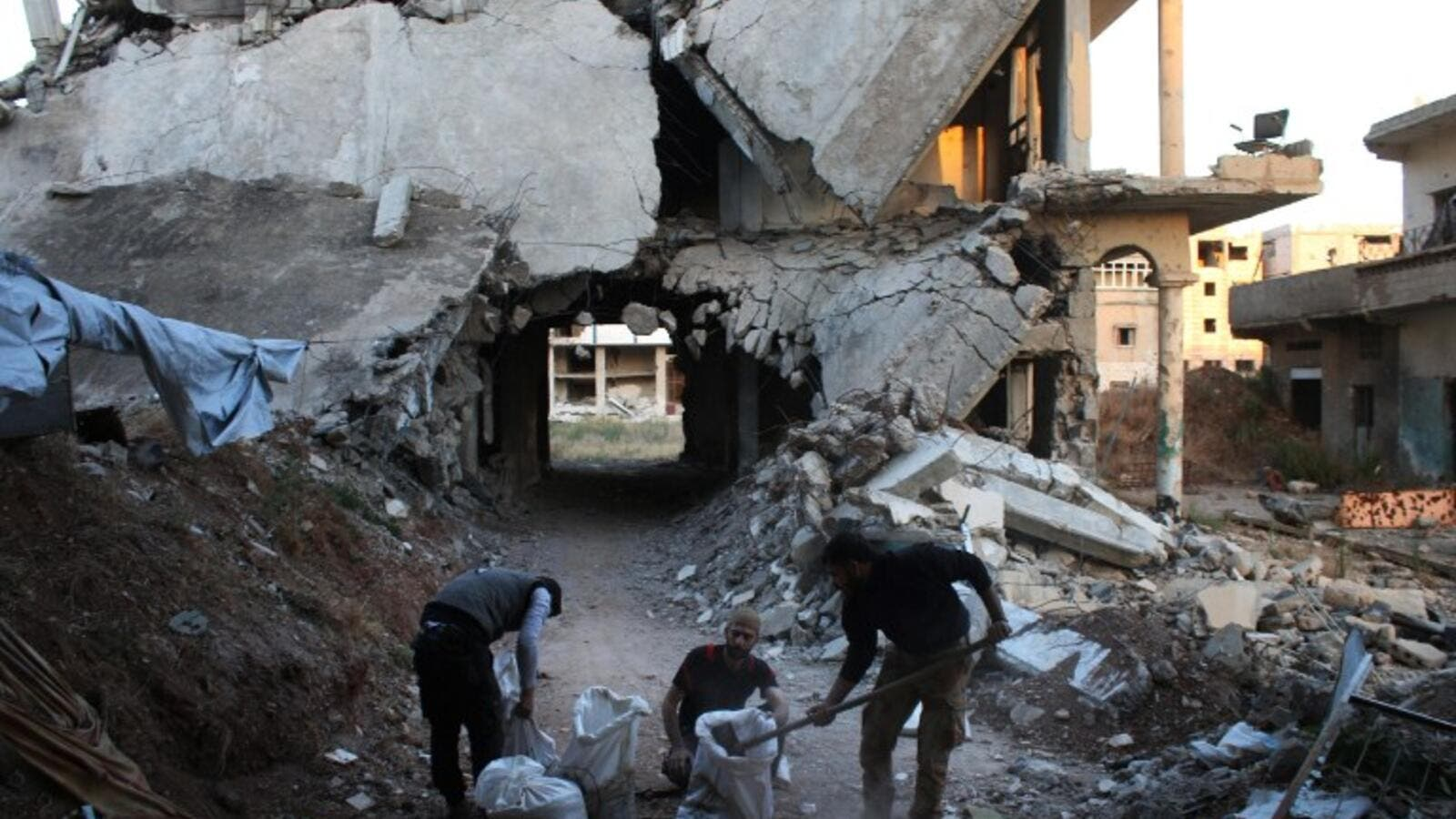 Rebel fighters fill bags with rubble from destroyed buildings they will use to strengthen a front-line position in a rebel-held area of Daraa, southern Syria, on May 18, 2016. (AFP/Mohammed Abazeed)