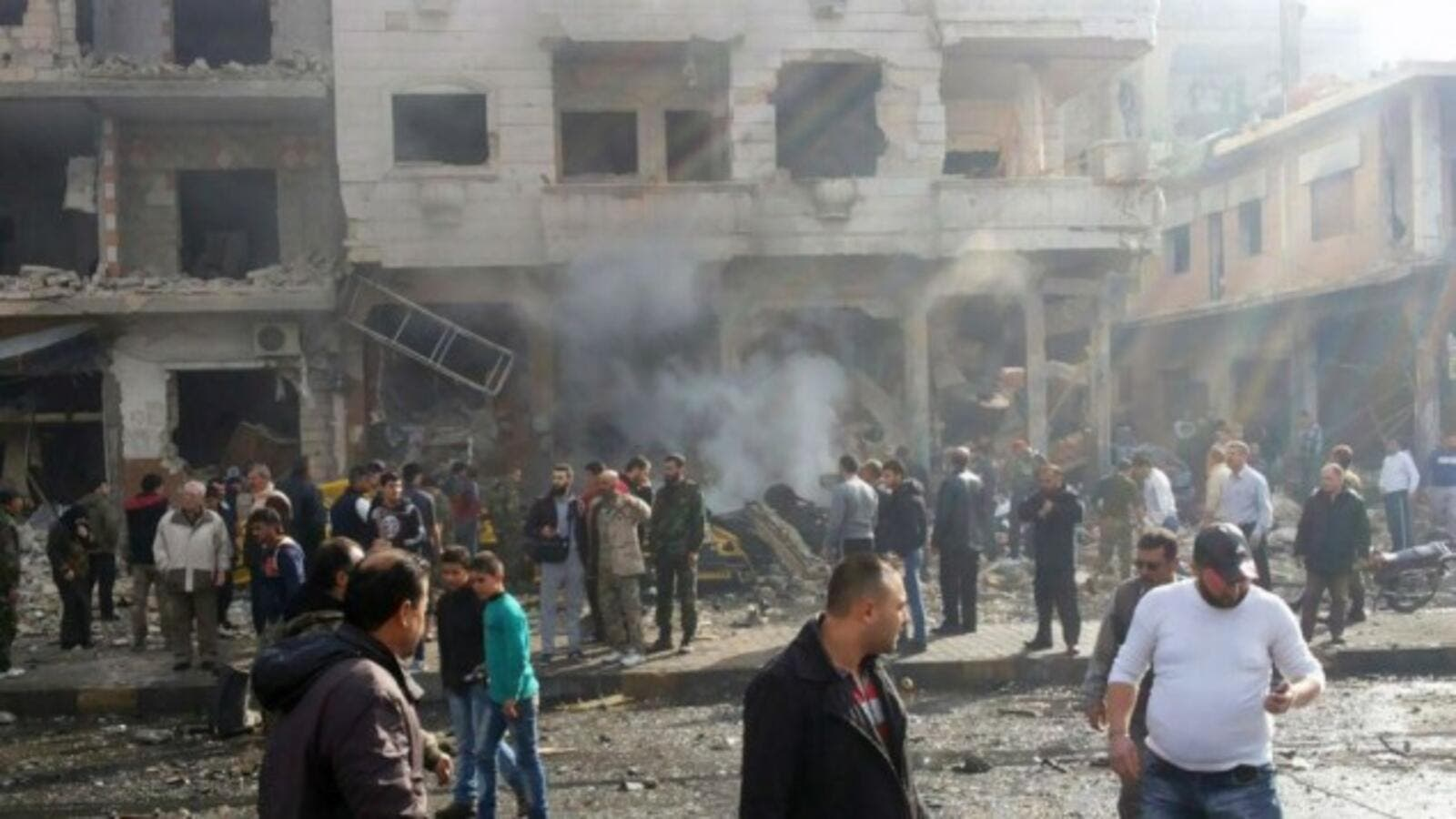 In this photo released by the Syrian official news agency SANA, residents gather at the scene where two blasts exploded in the pro-government neighborhood of Zahraa, in Homs province, Syria, Sunday, Feb. 21, 2016. (AFP/File)