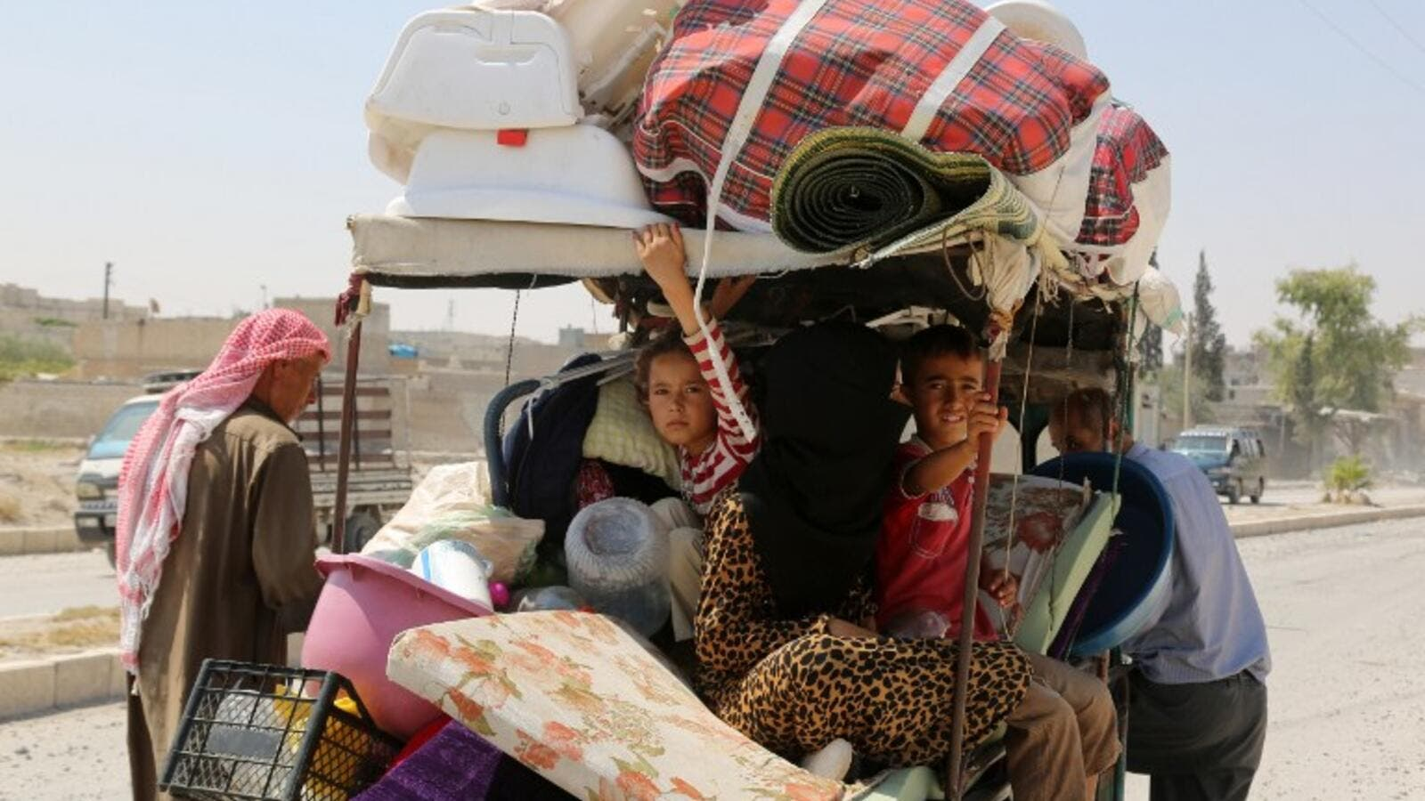 Syrian children sit in a cart, loaded with belongings, in the northern Syrian town of Manbij as civilians go back to their homes on August 14, 2016 after the Arab-Kurdish alliance, known as the Syrian Democratic Forces (SDF), pushed Daesh out of the city. (AFP/Delil Souleiman)