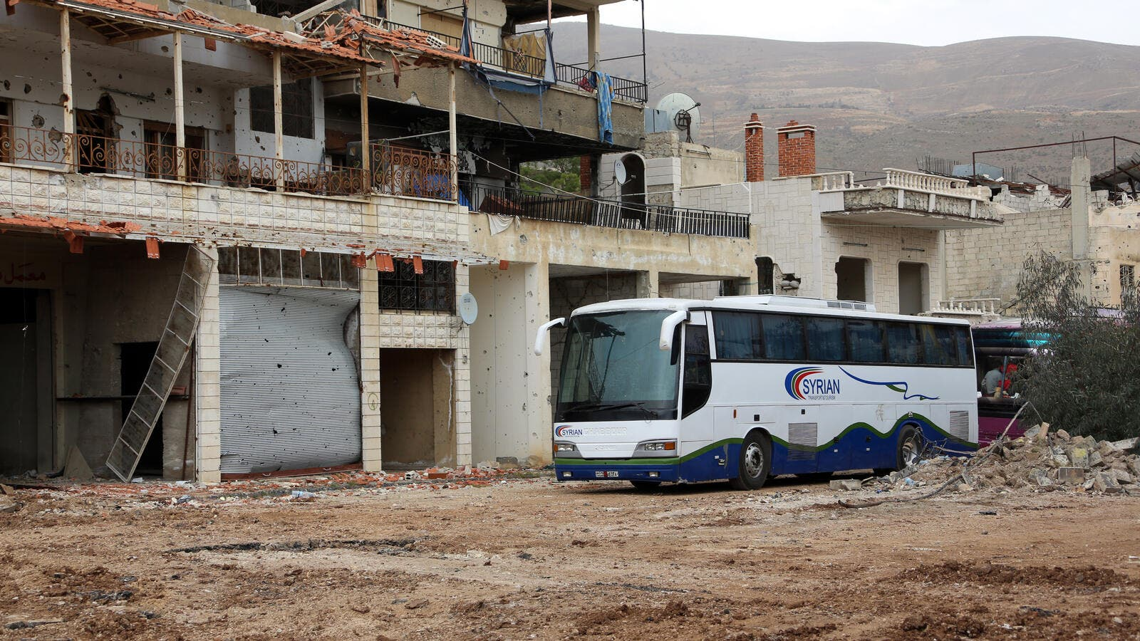 "A convoy of buses drives into the besieged oppositon-held town of Zabadani in preparation for the town's ""evacuation"", April 12, 2017. (AFP)"