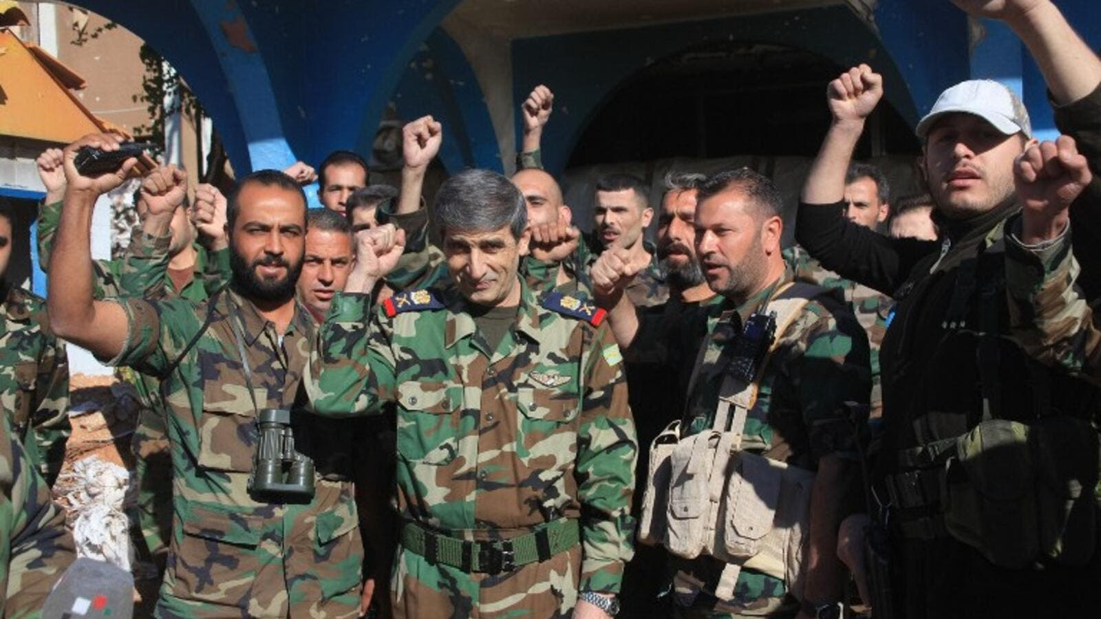 Members of the Syrian Army celebrate reclaiming the Kweires airbase earlier this week, shortly before recapturing Al-Hader, also in Aleppo. (AFP/George Ourfalian)