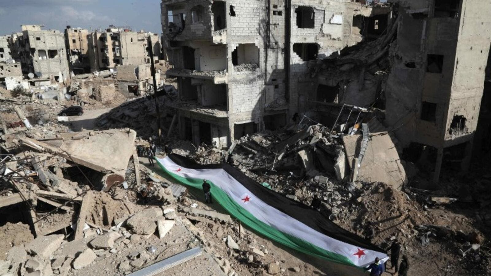 Residents and activists hold a giant a pre-Baath Syrian flag, now used by the Syrian opposition, during an anti-regime protest in the suburbs of Damascus. (AFP/Amer Almohibany)