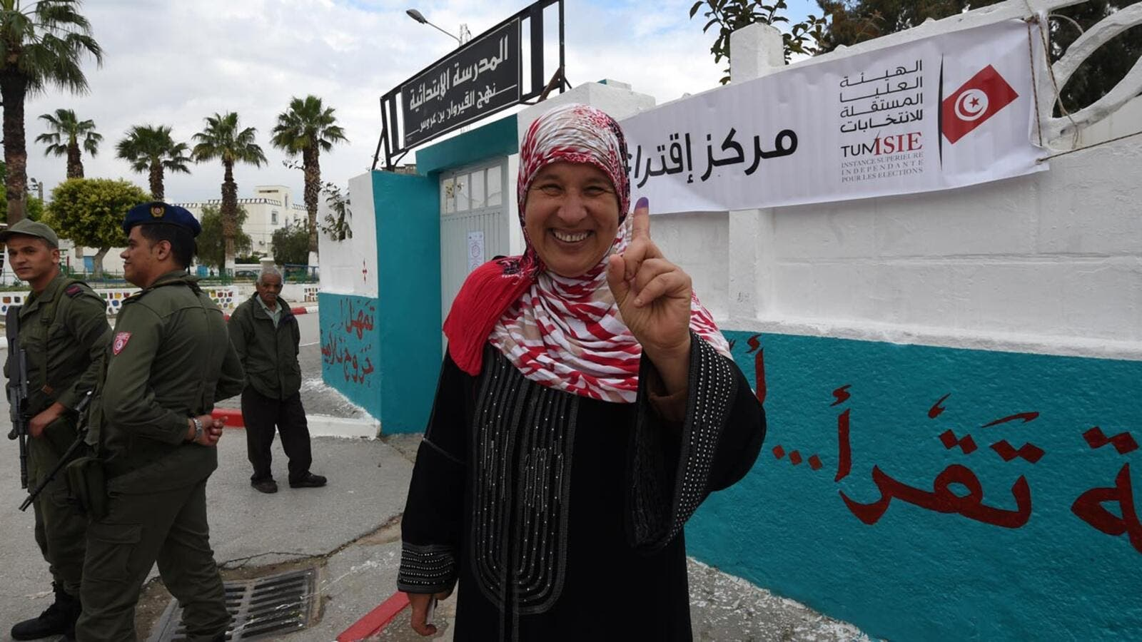 A Tunisian woman voter showcases her ink-stained index finger outside a polling station in Ben Arous near the capital Tunis on May 6, 2018. (AFP/File Photo)