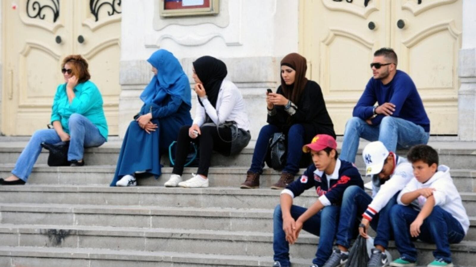 Young Tunisians sitting on the steps outside Habib Bourguiba Avenue in Tunis. (AFP/file)