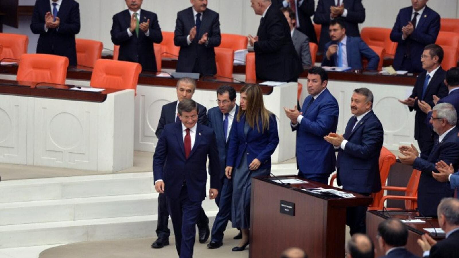 People applaud as Turkey's outgoing Prime Minister Ahmet Davutoglu (C) walks on May 17, 2016 during the discussions on the ruling AK Party's proposal regarding the amendment of the immunity at the Turkish Parliament in Ankara. (AFP/Adem Altan)