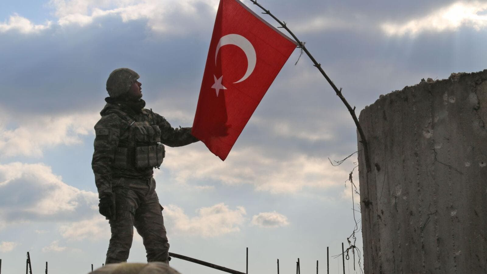 A Turkish soldier checks the national flag on a mountain on the Syrian-Turkish border, north of Azaz on Jan. 28, 2018. (AFP/ File)