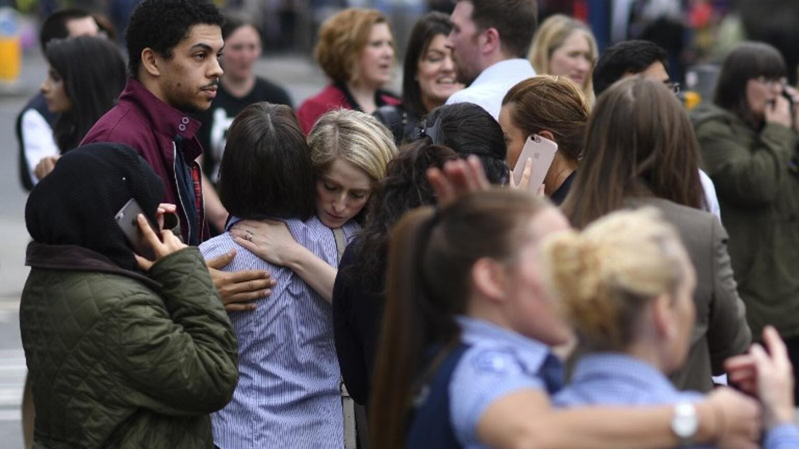 Retail staff hug each other after being evacuated from the Arndale Centre shopping mall in Manchester, northwest England on May 23, 2017 following a security alert the day after a deadly terror attack at the Manchester Arena. (AFP/Ben Stansall)