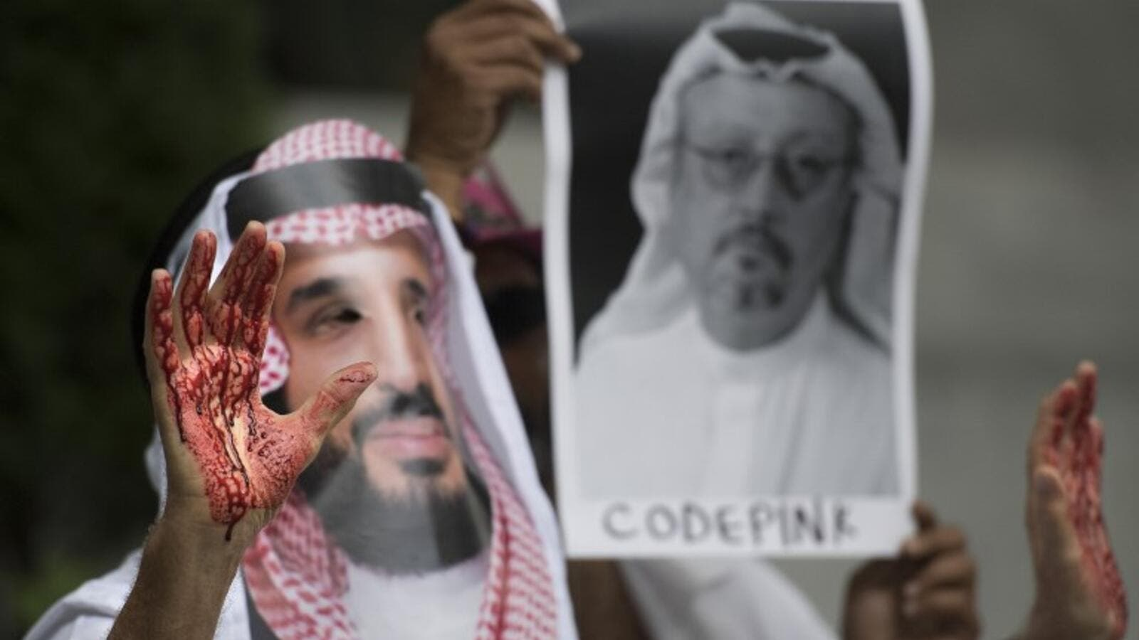A demonstrator dressed as Saudi Crown Prince Mohammed bin Salman with blood on his hands protests with others outside the Saudi Embassy in Washington, DC. (AFP/File)