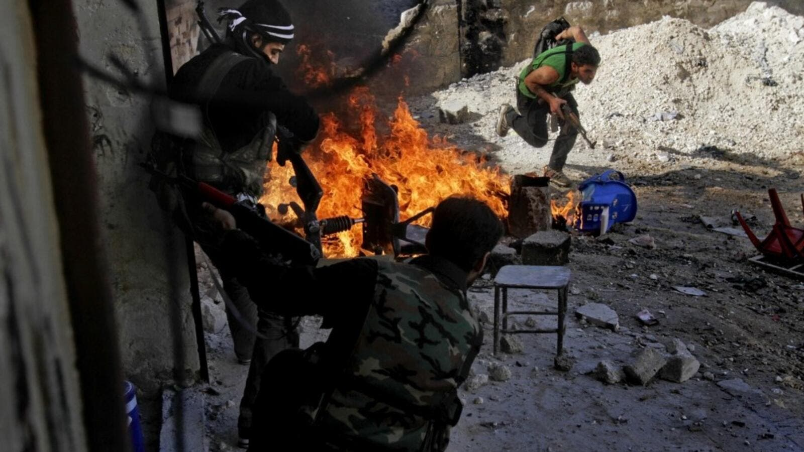 Syrian rebels of the Halab al-Shabah battalion under Al-Tawhid brigade take position during clashes with regime forces in Al-Amariya district of the northern city of Aleppo. (AFP/File)